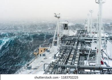 Big gas carrier sailing through an stormy arctic sea.