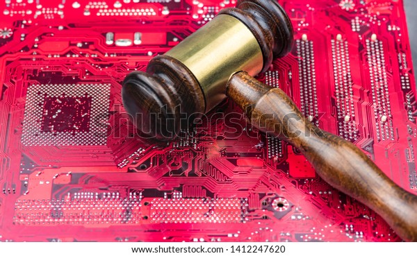 A big gavel over computer mainboard.Concept image law and judge for online internet