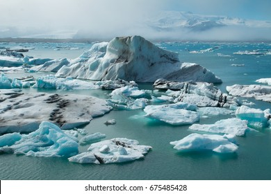 big glacier floating on a frozen lagoon with cool aqua blue water and a snow storm forming in the background in the arctic tundra of northern Iceland.