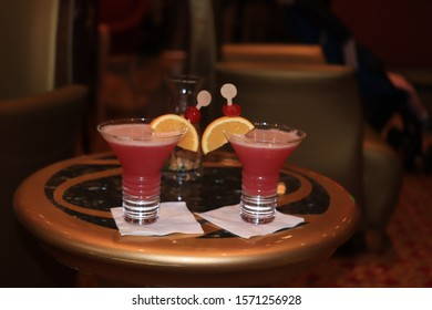 Big glass with a fruity cocktail, decorated with a wooden stirrer and fresh fruit. Cruise ship cocktail