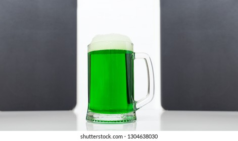 Big glass of green beer on the background gray board for text. St Patrick's Day holiday - poster concept.