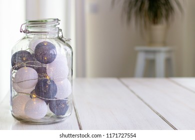 Big glass jar filled with lightning lampions standing on a wooden table