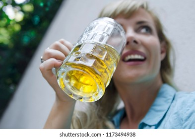 Big glass of light beer in girl hand.Woman drinking beer from beer mug, close up happy face.Beautiful female cheers with beer mug and smile