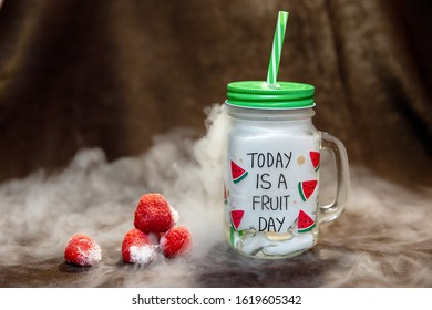 Big glass mug with water and dry ice and few frozen strawberries