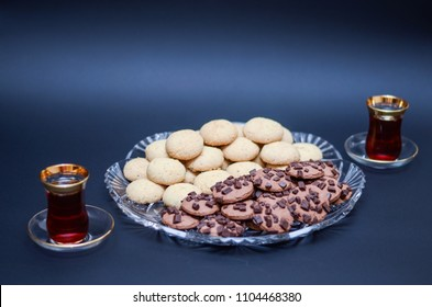 A big glass serving plate full of plain Kahk with no sugar (traditional Arabian cookies) and chocolate chips cookies and Turkish tea cups on a black background