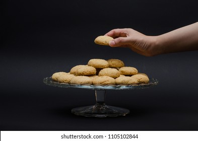 A big glass serving plate full of plain Kahk with no sugar (traditional Arabian cookies) and a female is grabbing one of the cookies on a black background