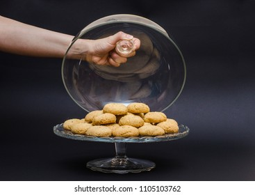 A big glass serving plate full of plain Kahk with no sugar (traditional Arabian cookies) and a female is grabbing the glass cover on a black background