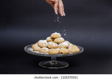 A big glass serving plate full of plain Kahk  (traditional Arabian cookies) and a lady sprinkle sugar powder on top of the kahk on a black background