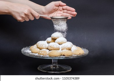 A big glass serving plate full of plain Kahk  (traditional Arabian cookies) and a lady sprinkle sugar powder from a sprinkler on top of the kahk on a black background
