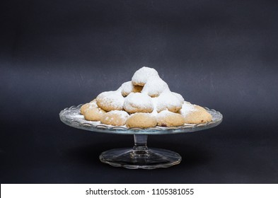 A big glass serving plate full of sugary Kahk  (traditional Arabian cookies)