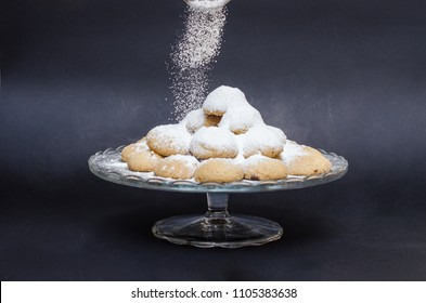 A big glass serving plate full of Kahk  (traditional Arabian cookies) and sugar getting sprinkled on top of the kahk on a black background