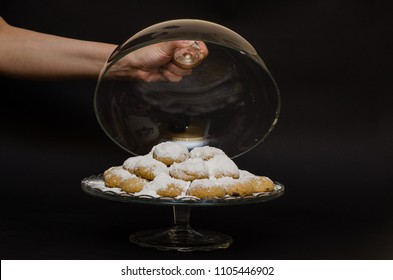 A big glass serving plate full of Kahk with (traditional Arabian cookies) with a cover glass bowel and a female is grabbing the handle