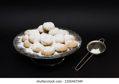 A big glass serving plate full of Kahk  (traditional Arabian cookies) and the sugar sprinkler is next to it.