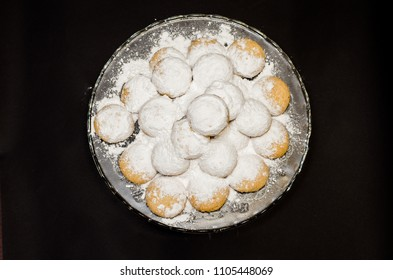 A big glass serving plate full of Kahk covered with sugar powder (traditional Arabian cookies)