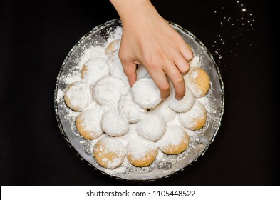 A big glass serving plate full of Kahk covered with sugar powder (traditional Arabian cookies) and a female hand is grabbing of the cookies