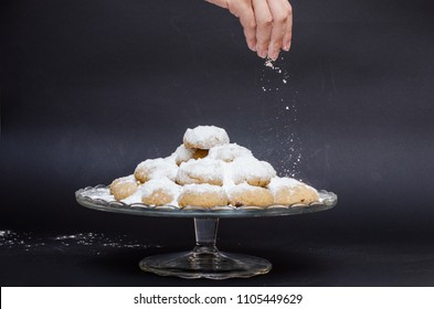 A big glass serving plate full of Kahk getting covered with sugar powder, sprinkled on top of it (traditional Arabian cookies)
