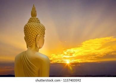 Big gold buddha statue with sunrise sky background.