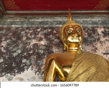 A big golden Buddha statue image with old mural painting wall in the background in Thailand .