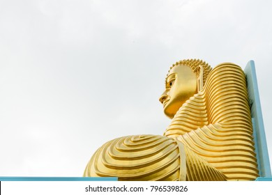 Big golden Buddha statue in wheel-turning pose on the top of a building with cloudy white sky on background