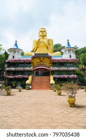 Big golden Buddha statue in wheel-turning pose on the top of Golden cave temple in Dambulla, Sri Lanka