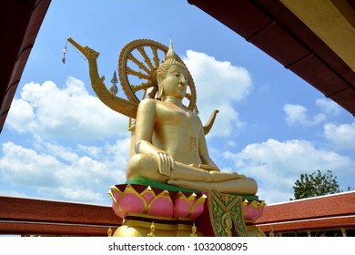 big golden buddha in temple with blue sky.