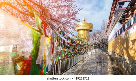 big golden prayer wheel with prayer flags and  cloudy blue sky background. at zhongdhian city shangri la yunnan china