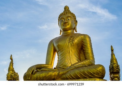 Big golden statue of Buddha on blue sky background