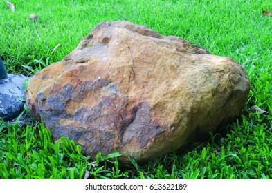 Big granite rock stone,Rocks on green grass.