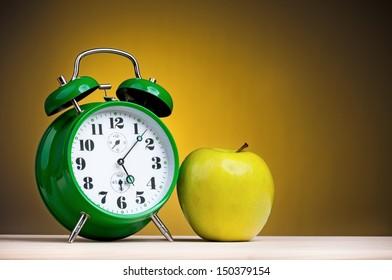 Big green alarm clock with apple on dark yellow background