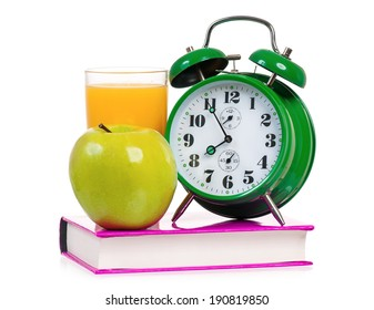 Big green alarm clock with apple, book and glass of orange juice, isolated on white background