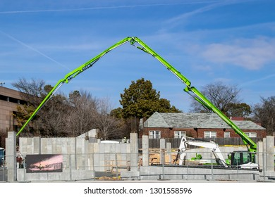Big green crane stretched across construction site with brick house showing through from behind - a few unrecognizable workers and a porta potty visible behind the concrete pillars