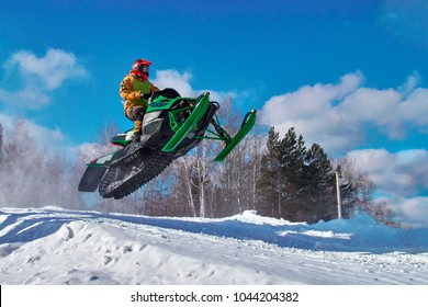 Big green Sport snowmobile jump. Cloud of snow dust from under snowmobile tracks. Copy space.