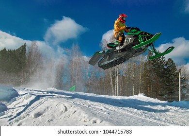 Big green Sport snowmobile jump. Cloud of snow dust from under snowmobile tracks. Concept extreme rest. Copy space.