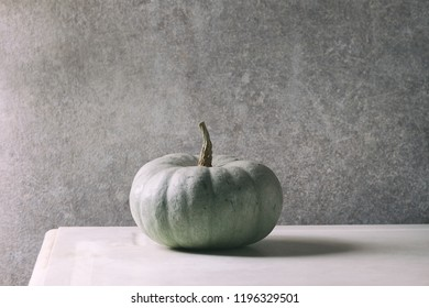 Big Grey whole uncooked pumpkin Confection on white marble table with grey wall at background. Autumn minimalist decoration.