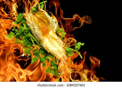 big grilled shrimp or prawn roast.with green coriander. On a black background. There is a hot fire burning shrimp. concept: menu food