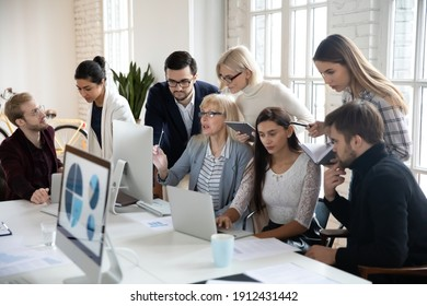 Big group of business people analyzing marketing reports on computers together. Crowded shared office work space. Busy diverse millennial team discussing project, brainstorming at workplaces