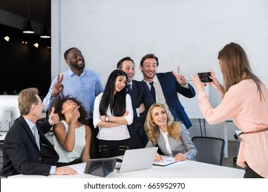 Big Group Of Business People In Office Together, Businesswoman Taking Photo Of Colleagues On Cell Smart Phone, Team Meeting Mix Race Coworkers Businesspeople Happy Smiling Sitting At Desk