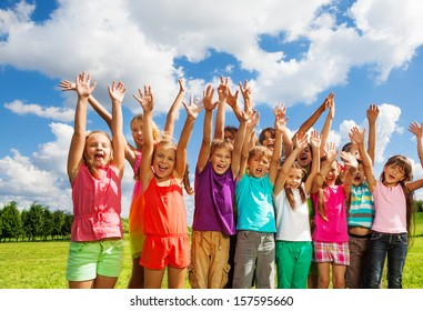Big group of children, boys and girls, 8-11 years old standing with happy faces and lifted hands on sunny summer day