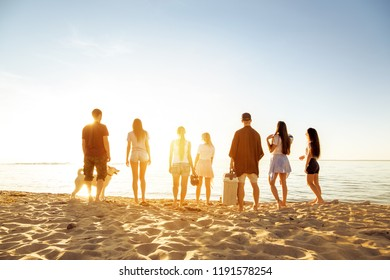 Big group of friends stands at sunset beach. Weekend picnic concept