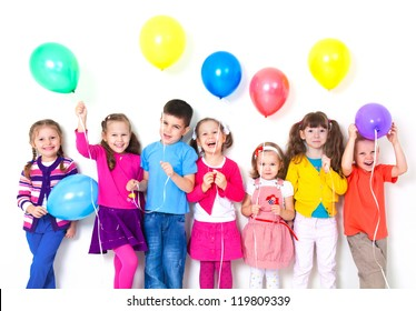 Big group of happy children with balloons at white wall