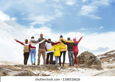 Big group of happy friends standing, hugging and looking at mountains. Travel concept