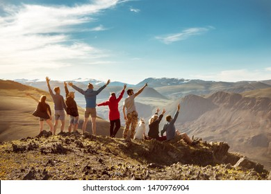 Big group of happy friends or tourists are having fun in mountains