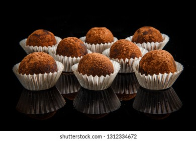 big group of healthy useful organic handmade round chocolate candies decorated with brown cocao powder on black mirror background