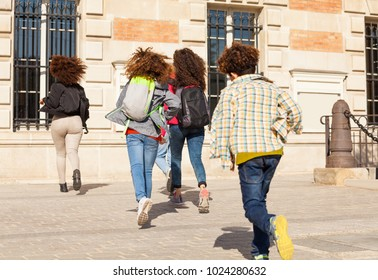 Big group of kids with backpacks running to school