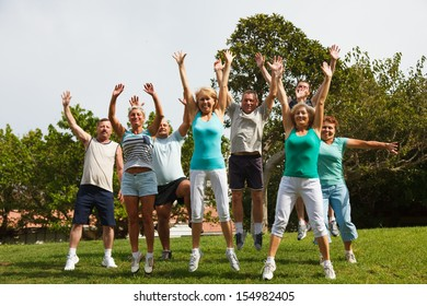 Big group of mature jumping people with hands up.
