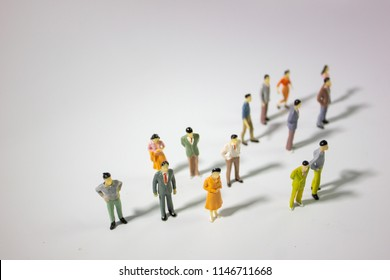 A big group of miniature business people stand on gray background top side view.