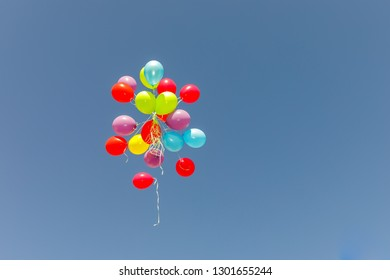 Big group multicolored balloons flying at blue sky