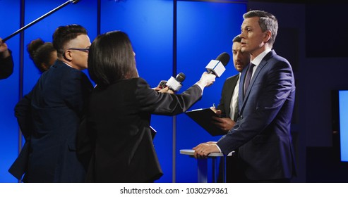 Big group of multiracial journalists with microphones and other technological equipment having interview with middle-aged politician in underlit studio.