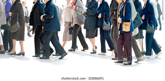The big group of older persons.  People walking against a light background.