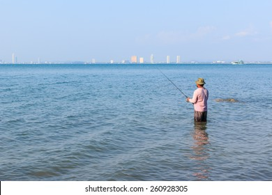 The big guy standing on the beach fishing in the sea
